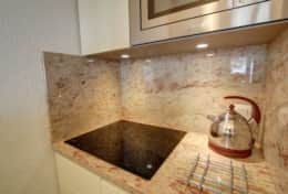 The kitchen features elegant marble worktops and wall panels.