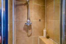 large steam shower with limestine bench