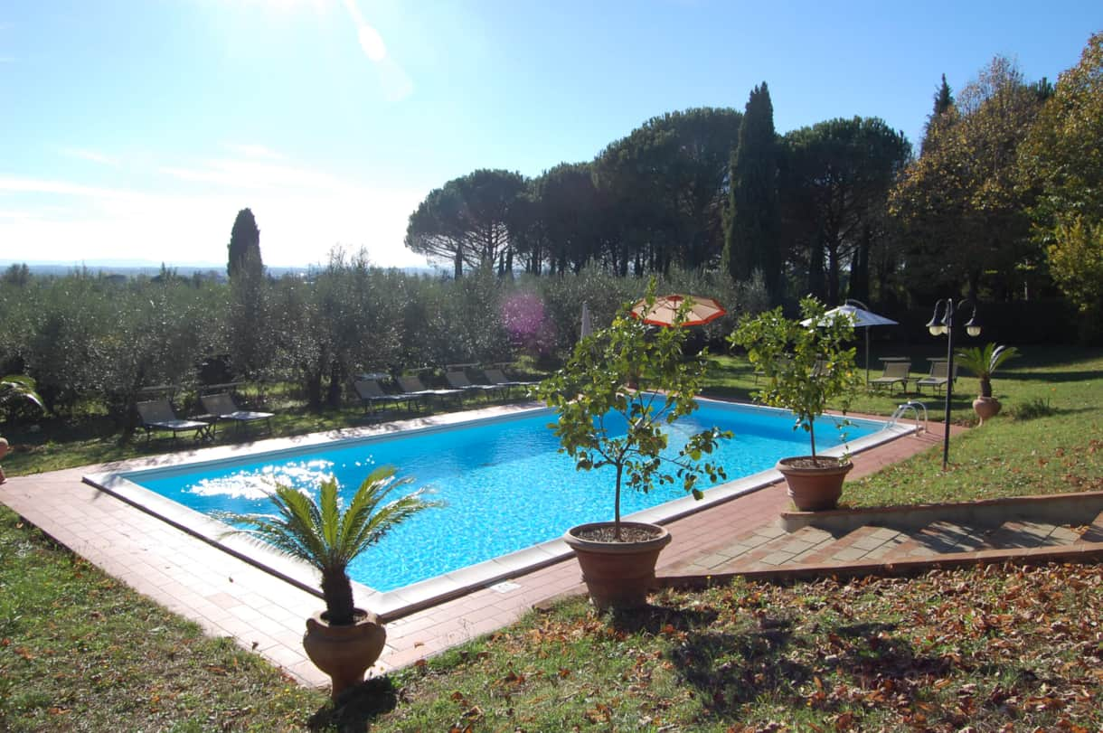 The pool house terrace has a beautiful view over the olive grove to the Tuscan hills over the valley