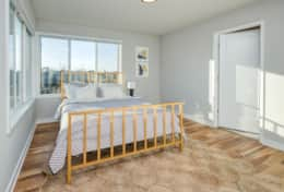Large corner windows and a queen-size bed are featured in the 2nd bedroom of Unit 4.