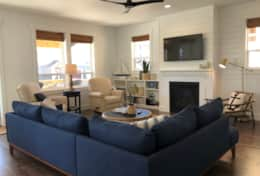 Ocean view main level living room has seating for seven or more adults, with additional stools.